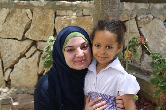 Malak, 5 years old, with her teacher Fawz.
