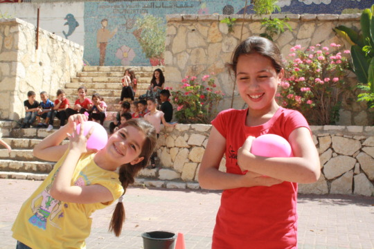 Students Hoor &Yasmine smile with their balloons.