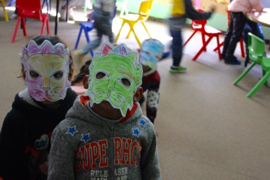 Students show off their lion masks in EFL class.