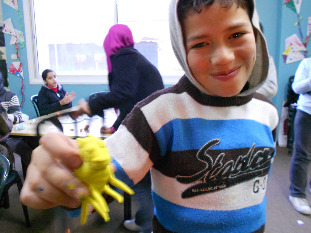 A proud student makes a clay animal in art class