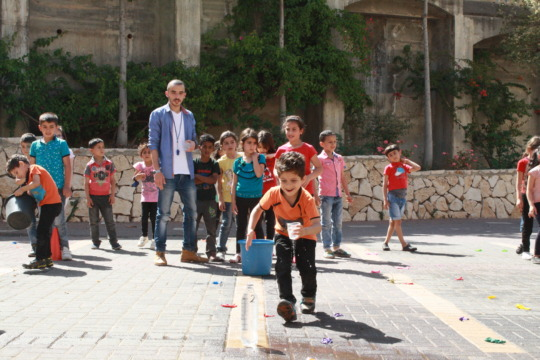 Student Zain smiles as he runs to fill the bottle.