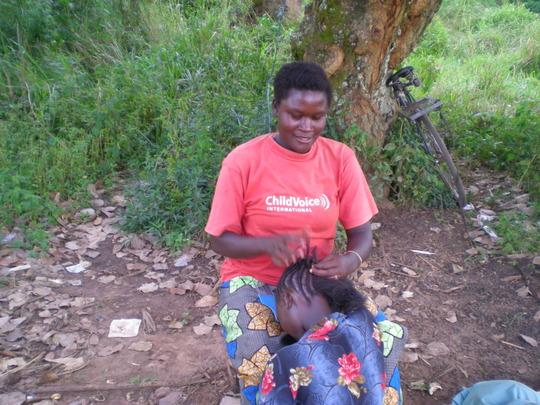 Rhema braiding a customer's hair