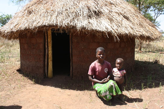 Scovia and son Isaac with the hut from money saved