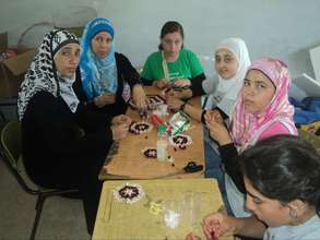Women and youth create crafts at summer camp.