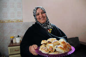 Ilham holds a tray of Mo'ajanat, a rolled pastry.