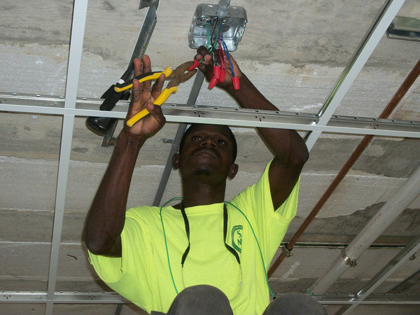 A Haitian electrician caps the ends of wires