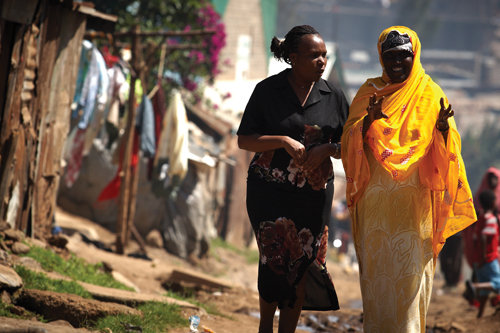 Jane Otai, left, speaks with woman in Nairobi