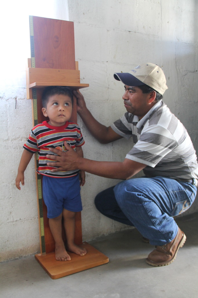 Health promoter, Rogelio, measures a child
