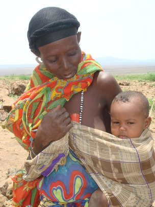 An Ethiopian woman walking with her baby and camel