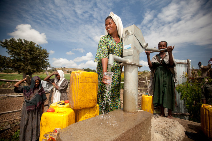 Women in a rural community gather clean water from a charity: water project. charity: water projects help reduce time spent collecting water, offering women a chance to earn an income.