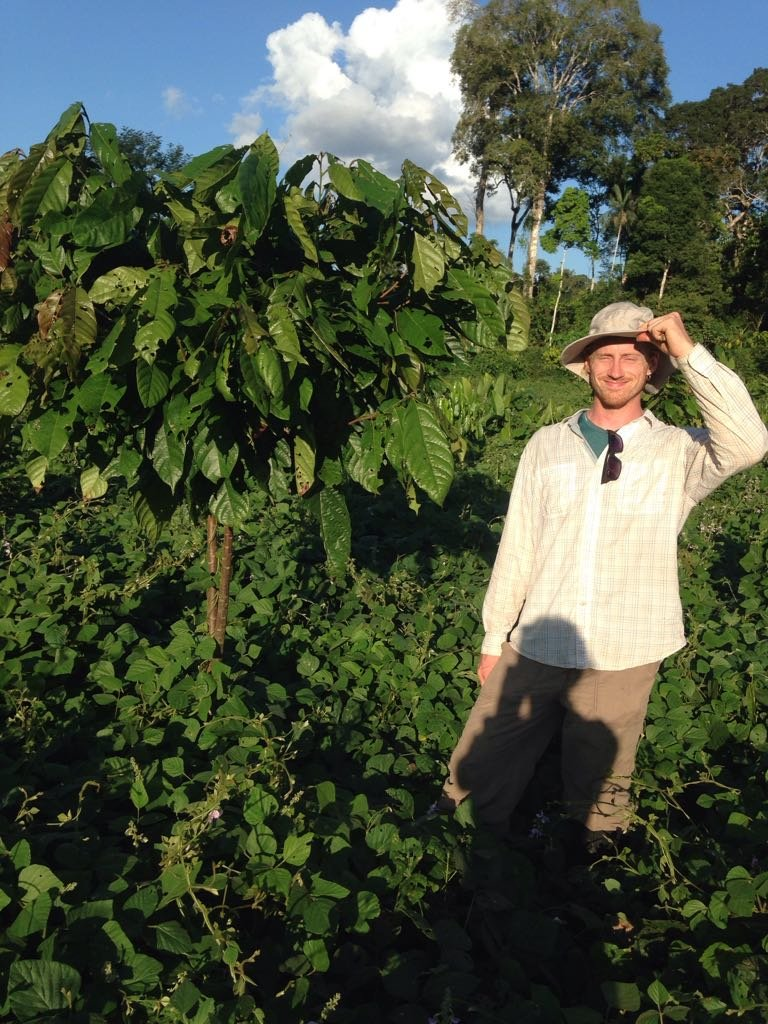 Ryan Smith with a cacao tree he planted in 2017