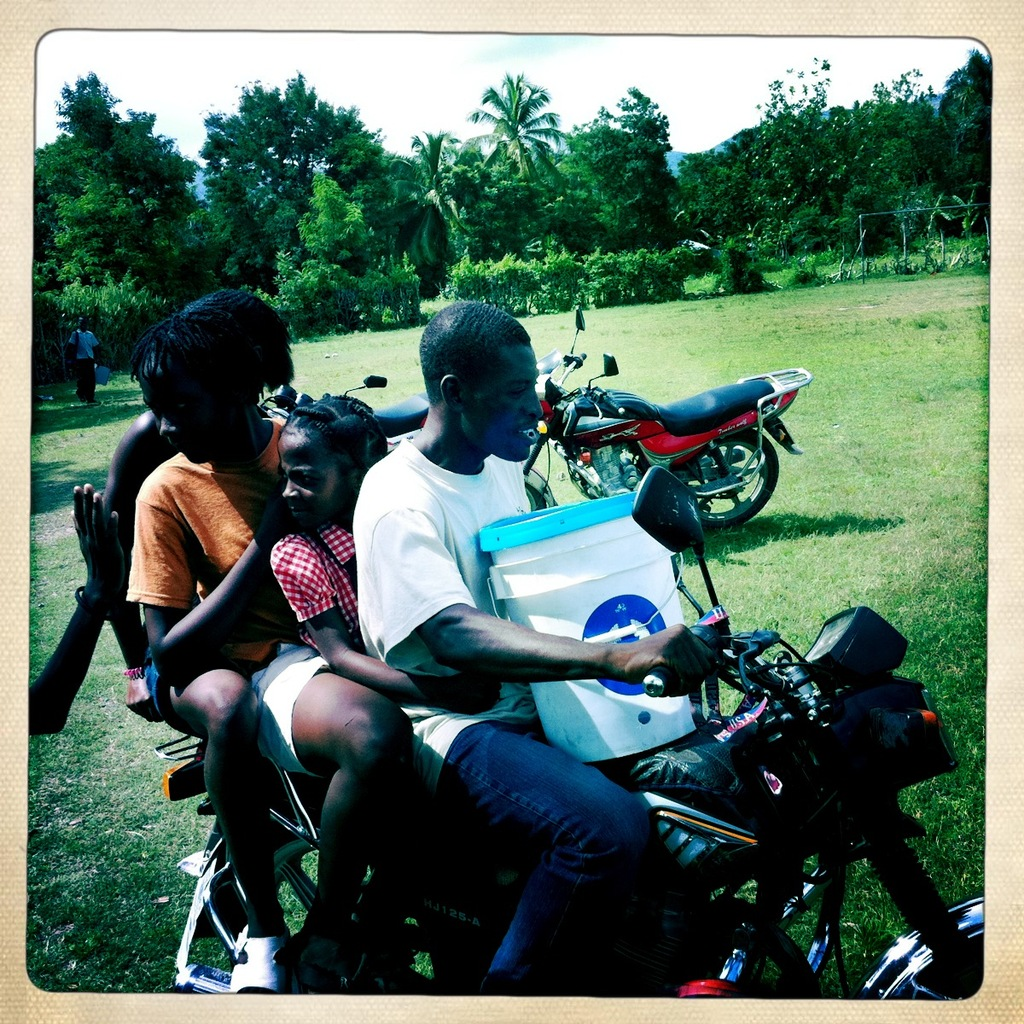 family on motorcycle with water