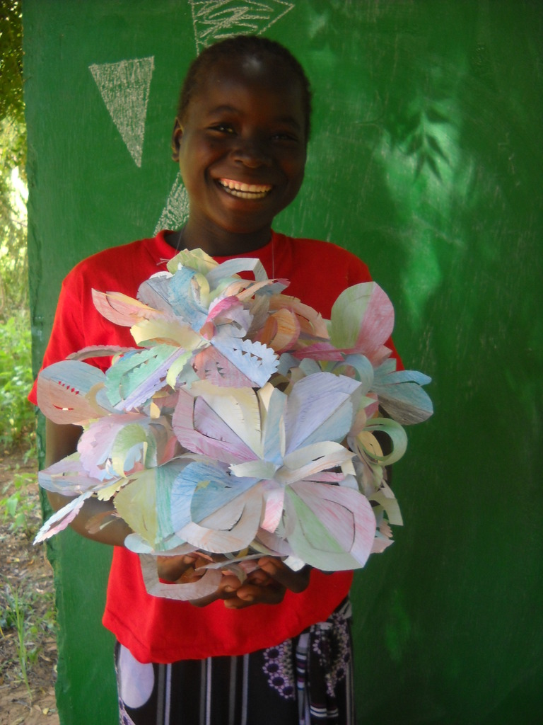 Student showing off flowers from a craft session