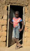 Young boy in the doorway of his home