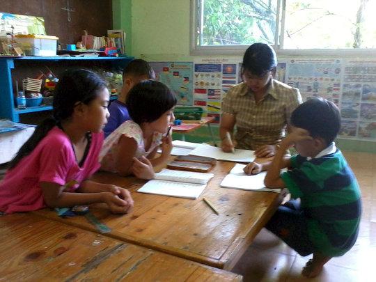 Ms. Lasang correcting the students homework