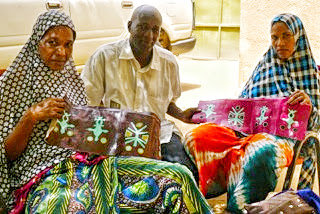 Illia working on handbags with artisans.