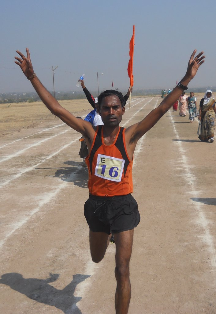 D.T. Dhebe raises his arms after winning the 10km