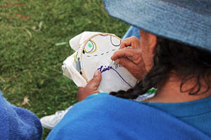 Dona Luisa is embroidering his name