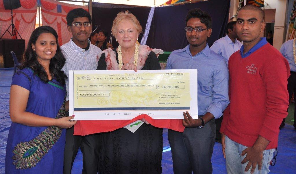 CHI graduates present a check to Christel DeHaan