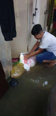KE staff fortifies his home's door with sandbags