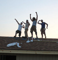 Volunteers pose on the roof of the new cat house