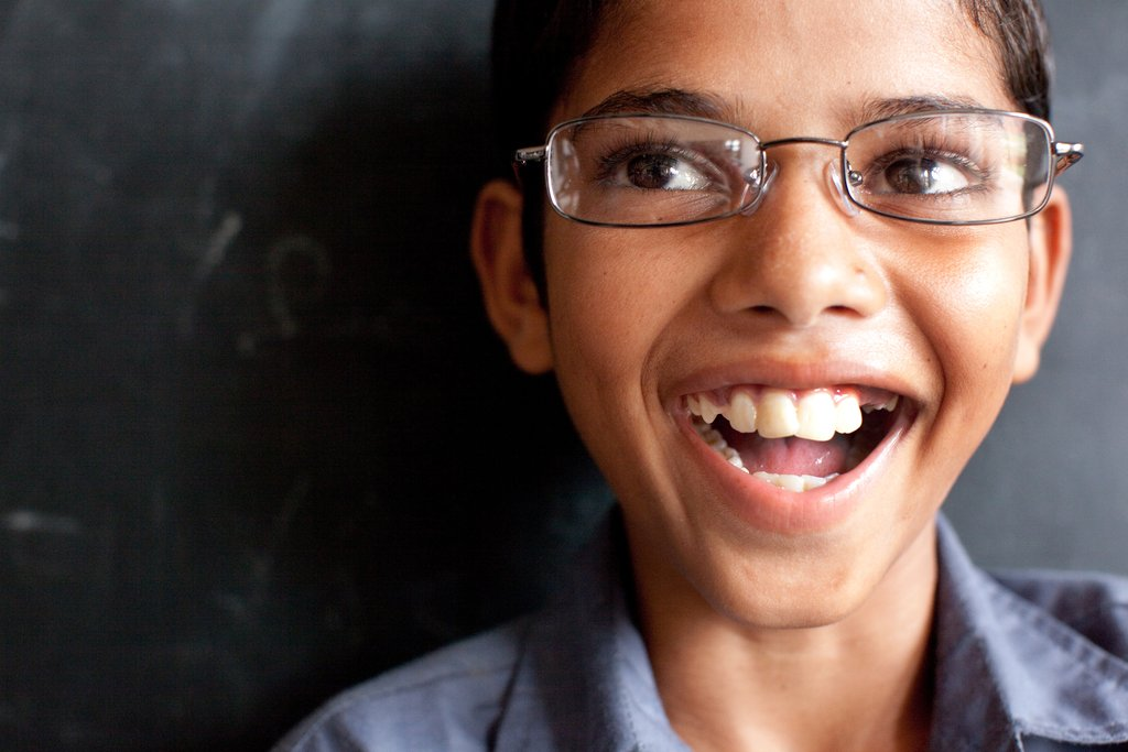 Krishan is smiling about his newly purchased pair of glasses. Students around the world struggle to see the blackboard, falling behind in school and dropping out. We are working hard to increase access to affordable glasses to students to give them the opportunity to succeed. (Credit Esther Havens)