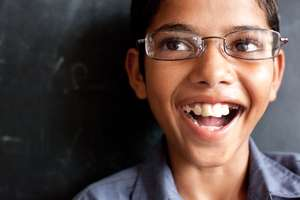Krishan, a student smiling about his new glasses.