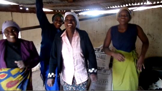 Women Dancing After Receiving Chicken Feed