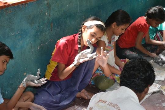 A Child appreciating her Clay model
