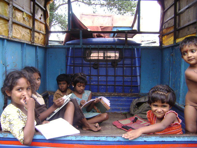 A quite place for study is very  rare in slums. In this picture , some children find it ( a small tempo parked near their house ) a better place to study than their tiny & congested tin sheet hut.