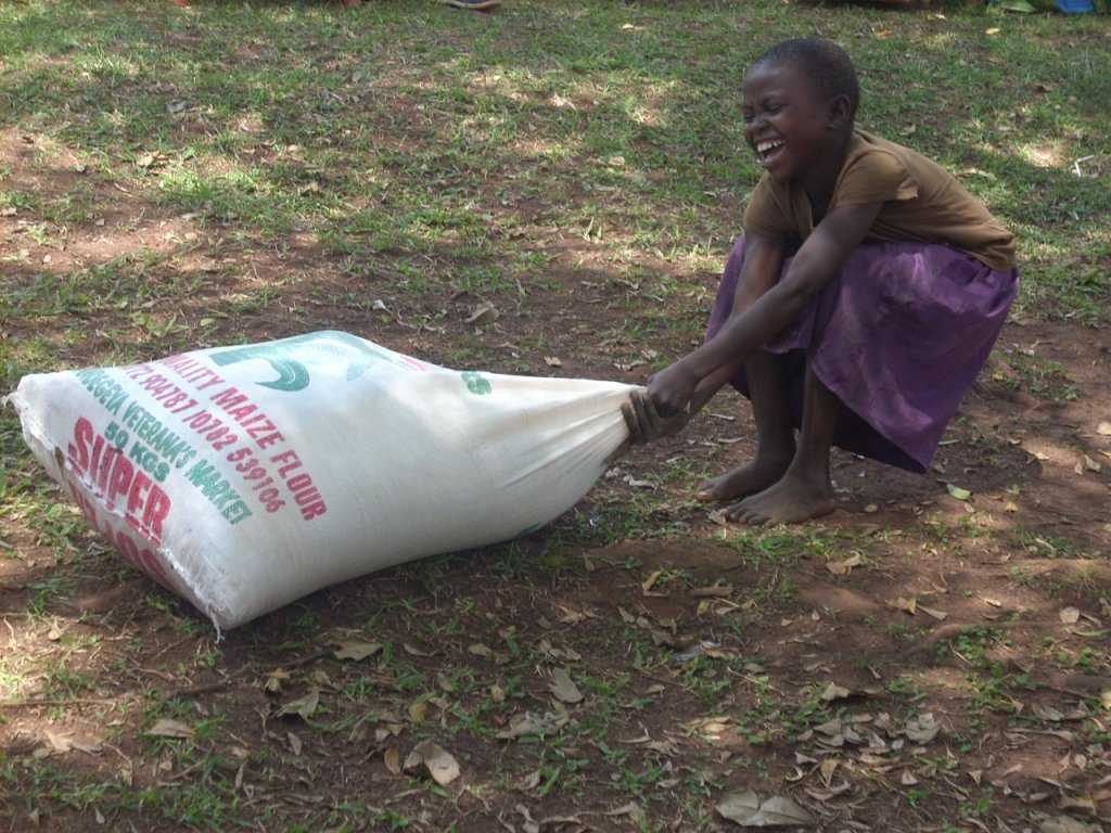 Nalumu Jeska,an Orphan at Kiwologma orphanage center Was happy and excited after we purchased food for the orphans and she decided to pull the bag of maize flour alone towards the Kitchen as a way of helping the cooks to prepare their meal(orphans )soonest possible.