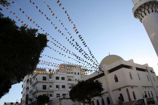 Libyan flags fluttter from a mosque in Tripoli