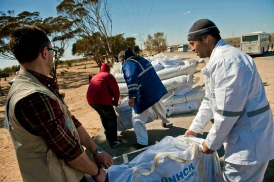 UNHCR and Tunisian volunteers carry tents