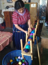 Juanita gets her thread ready to weave.
