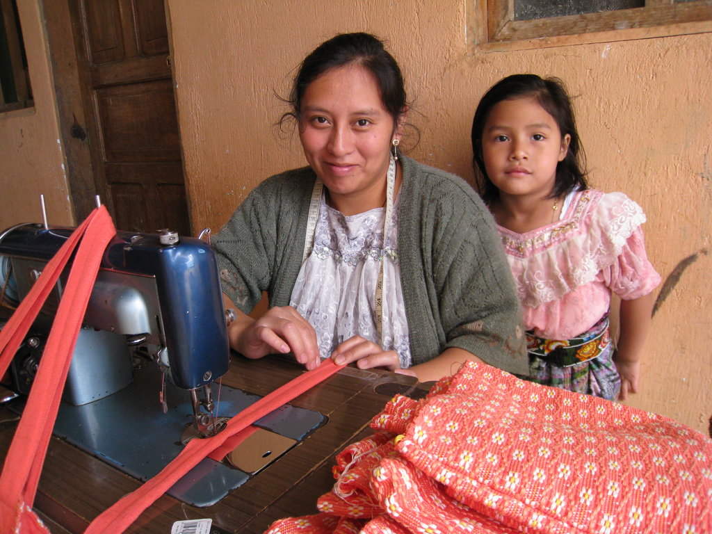 Silvia sews baby products in Comalapa, Guatemala while her daughter Natalia spends some quality time with her mother after school.  Silvia is a great role model for Natalia.  She works hard so that her daughter can attend school which means Natalia will have many more options in her future.