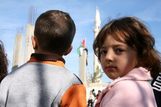 Children watching the Palestinian flag be raised