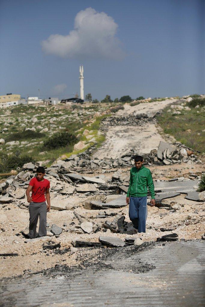 Youth standing on demolished road to Aqaba