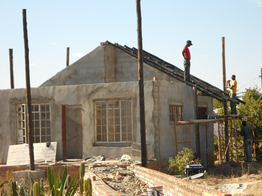 Foster & Tinashe installing roof on cottage