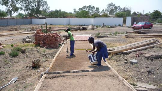 Sithibisiwe preparing path for brick. Her project.