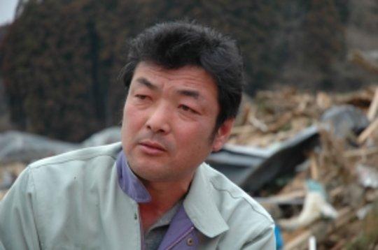 Fuminori Onodera sits among ruins in Shizugawa