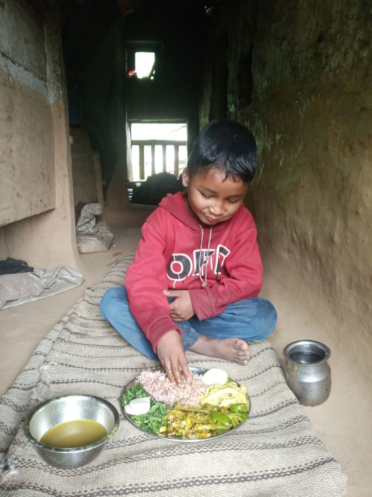 A child having greens and mushrooms in Bajura