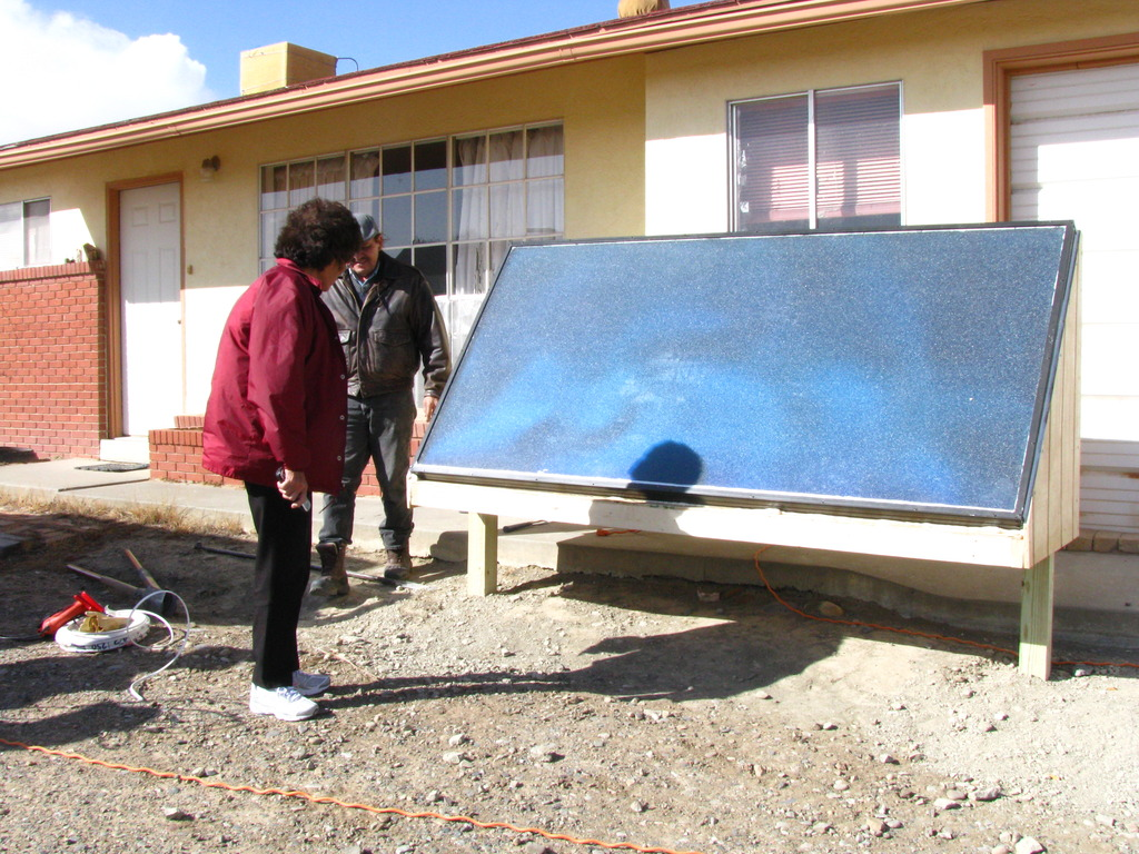 Eva Stokely inspects her new solar air heater