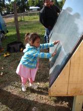 Jessa, solar heater recipient, warms to her panel