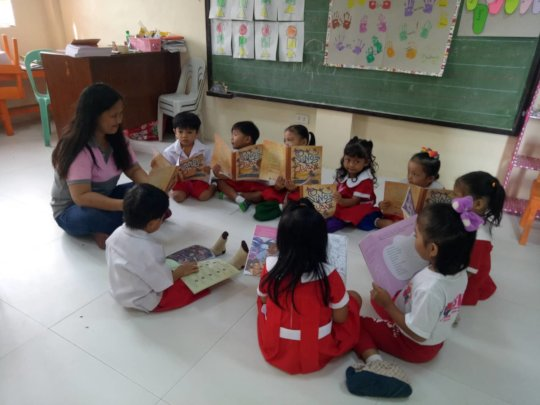 Children gather around for a little book-reading