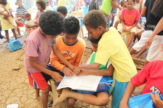 Aeta children working on the book activity pages.