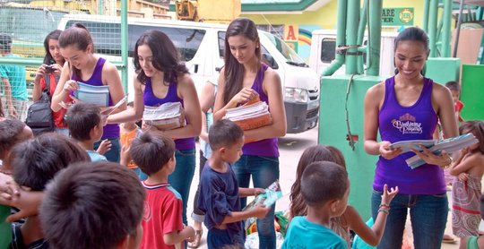 Four Miss Philippines winners giving out books