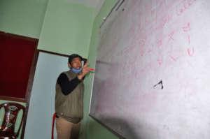 Harilal Limbu demonstrating how to write Limbu