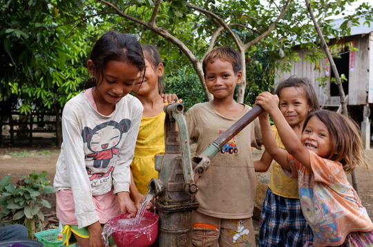 Children get water from a well on cleared ground.