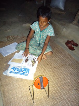 Geetika studying by the light of the solar lamp