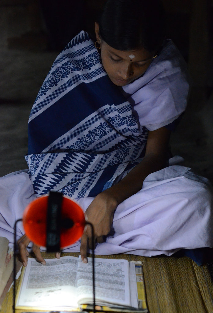 Hasina Khatun using her new solar lamp